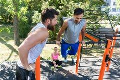 Zwei muskulöse junge Männer, die Körpergewicht tun, trainiert im Eignungspark stockfotografie