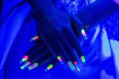 Zwei Neonhände mit langen Nägeln Stockfoto