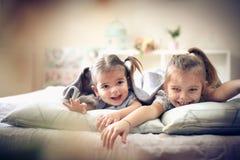 Zwei nett kleine Mädchen im Bett lizenzfreie stockfotografie
