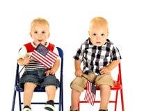 Zwei nette blonde Jungen, die das Sitzen der amerikanischen Flaggen halten Stockbild
