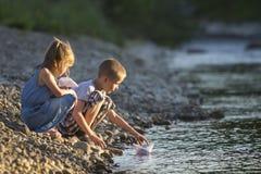 Zwei nette blonde Kinder, Junge und Mädchen auf der Flussbank, die in w sendet Stockfotografie
