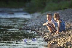 Zwei nette blonde Kinder, Junge und Mädchen auf der Flussbank, die in w sendet Lizenzfreies Stockfoto
