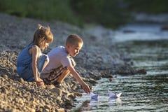 Zwei nette blonde Kinder, Junge und Mädchen auf der Flussbank, die in w sendet Stockfotos