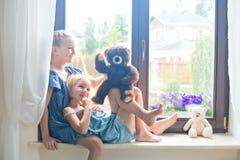 Zwei nette europäische Kleinkindmädchen, die Spielwaren spielen, nähern sich Fenster zu Hause lizenzfreie stockfotografie
