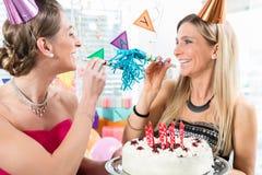 Zwei nette Frauen und beste Freunde, die einen Geburtstagskuchen halten Lizenzfreies Stockfoto