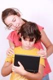 Zwei nette Freundinnen blicken in Laptop Lizenzfreies Stockbild