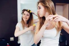Zwei nette Freundinnen, die zu Hause ihr Haar in Lockenwickler einsetzen Stockfoto