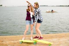Zwei nette glückliche Schlittschuhläufermädchen in der Hippie-Ausstattung, die Spaß auf einem hölzernen Pier während der Sommerfe stockfoto