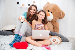 Zwei nette glückliche Schwestern, die Laptop im Kinderraum verwenden Lizenzfreie Stockfotografie