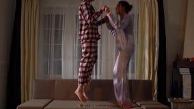 Zwei nette glückliche Schwesterzwillinge in den pajams, die auf die Couch in einem gemütlichen Wohnzimmer springen und Spaß wie i stock video