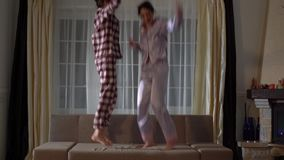 Zwei nette glückliche Schwesterzwillinge in den pajams, die auf die Couch in einem gemütlichen Wohnzimmer springen und Spaß wie i stock footage