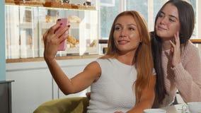 Zwei nette junge Frauen, die selfies an der Kaffeestube nehmen stock video