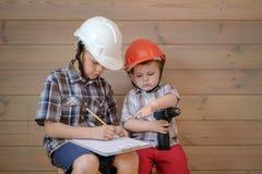 Zwei nette Jungen in den Bausturzhelmen besprechen einen Plan f?r die bevorstehende Arbeit Kinder spielen Erbauer lizenzfreie stockfotos