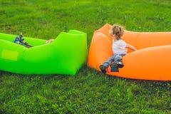 Zwei nette Jungen, die auf einem Luftsofa im Park stillstehen stockbilder
