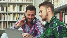 Zwei nette Kerle verbringen ihre Freizeit in der Bibliothek stock video