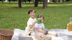 Zwei nette Kinder, die draußen Getränke sitzen und trinken