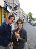 Zwei nette Kinder mit Brillen essen die Pommes-Frites Lizenzfreie Stockfotografie