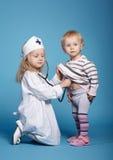 Zwei nette kleine Mädchen, die Doktor spielen Stockfotografie