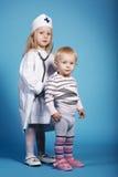 Zwei nette kleine Mädchen, die Doktor spielen Stockbild