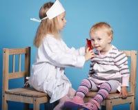 Zwei nette kleine Mädchen, die Doktor spielen Lizenzfreies Stockfoto