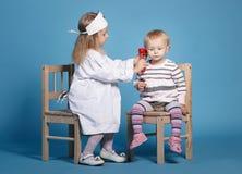 Zwei nette kleine Mädchen, die Doktor spielen Lizenzfreie Stockfotografie