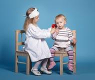 Zwei nette kleine Mädchen, die Doktor spielen Stockbilder