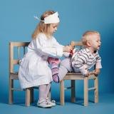 Zwei nette kleine Mädchen, die Doktor spielen Stockfotos