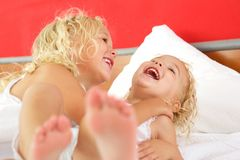Zwei nette kleine Mädchen, die zusammen auf Bett spielen Stockbild