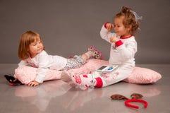 Zwei nette kleine Schwestern in den weißen Pyjamas Lizenzfreie Stockbilder