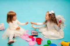 Zwei nette kleine Schwestern, die mit Spielwaren spielen Stockfoto