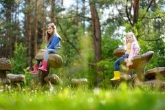 Zwei nette kleine Schwestern, die Spaß auf riesigen hölzernen Pilzen haben stockbild