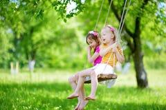 Zwei nette kleine Schwestern, die Spaß auf einem Schwingen zusammen im schönen Sommergarten haben Stockfotos