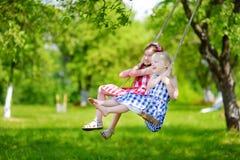 Zwei nette kleine Schwestern, die Spaß auf einem Schwingen zusammen im schönen Sommergarten haben Lizenzfreie Stockbilder