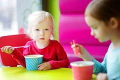 Zwei nette kleine Schwestern, die zusammen Eiscreme essen Stockfotos