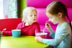 Zwei nette kleine Schwestern, die zusammen Eiscreme essen Lizenzfreies Stockbild
