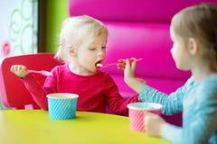Zwei nette kleine Schwestern, die zusammen Eiscreme essen Lizenzfreie Stockfotografie