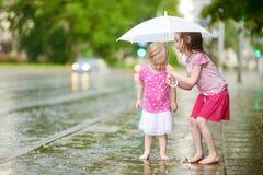 Zwei nette kleine Schwestern an einem regnerischen Sommertag Stockfoto