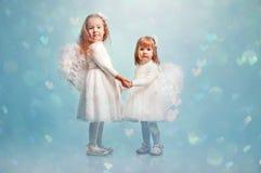 Zwei nette kleine Schwestern mit den Flügeln eines Engels Lizenzfreies Stockfoto