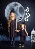 Zwei nette kleine Schwestern werden in den Hexenkostümen gekleidet Stockbilder