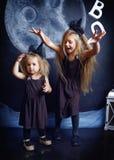 Zwei nette kleine Schwestern werden in den Hexenkostümen gekleidet Lizenzfreie Stockfotografie