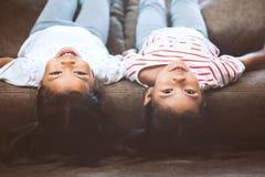 Zwei nette kleines Kindermädchen liegen auf ihren Rückseiten auf Sofa lizenzfreie stockfotos