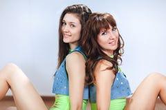 Zwei nette lächelnde Brunettemädchen oder -frauen in der Denimweste sitzen zurück zu der Rückseite und betrachten die Kamera, Nah Lizenzfreie Stockfotos