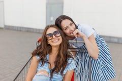 Zwei nette lächelnde dünne dunkelhaarige Damen, tragende zufällige Ausstattung, haben Spaß mit einem Lebensmittelgeschäftwagen na stockfotografie