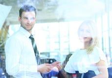 Zwei nette lächelnde junge Wirtschaftler, die im Büro sprechen Lizenzfreie Stockfotos