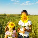 Zwei nette litle Mädchen, die hinter Sonnenblumen sich verstecken Stockbilder