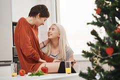 Zwei nette Mädchen, die in der Küche bei der Unterhaltung und dem Lachen während des Frühstücks nahe Weihnachtsbaum sitzen Typisc lizenzfreies stockbild