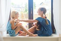 Zwei nette Mädchen, die Spielwaren auf Schwelle nahe Fenster am Haus spielen Stockfotos