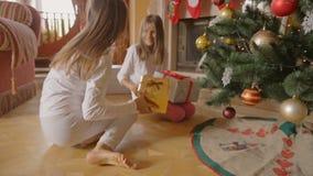 Zwei nette Mädchen, die zu den Geschenken unter Weihnachtsbaum am Morgen laufen stock video footage