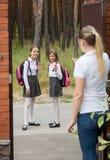 Zwei nette Mädchen, die zur Schule am Mnorning und am Wellenartig bewegen, um zu bemuttern verlassen Lizenzfreie Stockfotos