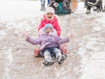Zwei nette Mädchen reiten eine Achterbahn des Eises Stockbild